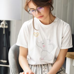 cute baby elephant with heart t-shirt of a woman reading at home