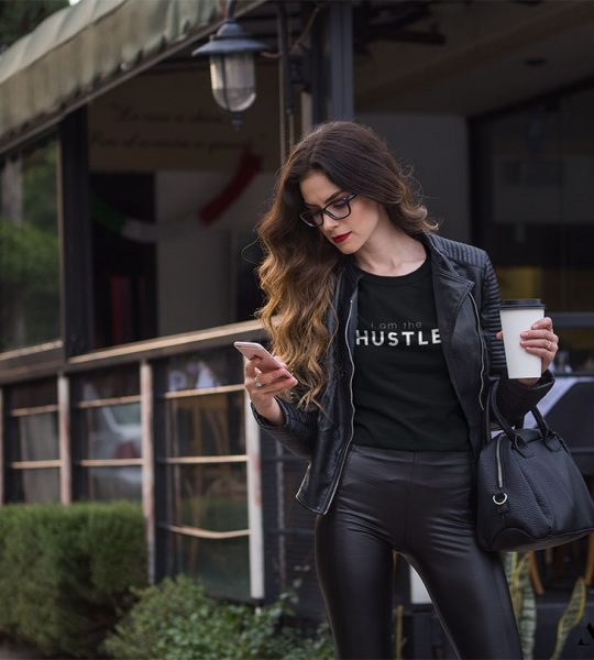 awesome vibe business woman wearing i am the hustle t-shirt while checking her phone outside a restaurant